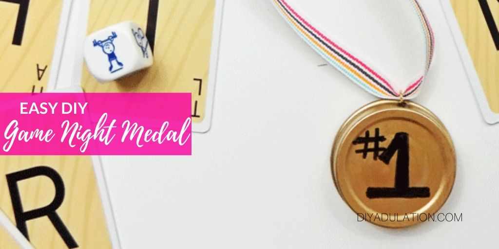 Close Up of Game Night Medal next to Cards and Die with text overlay - Easy DIY Game Night Medal - DIY Adulation