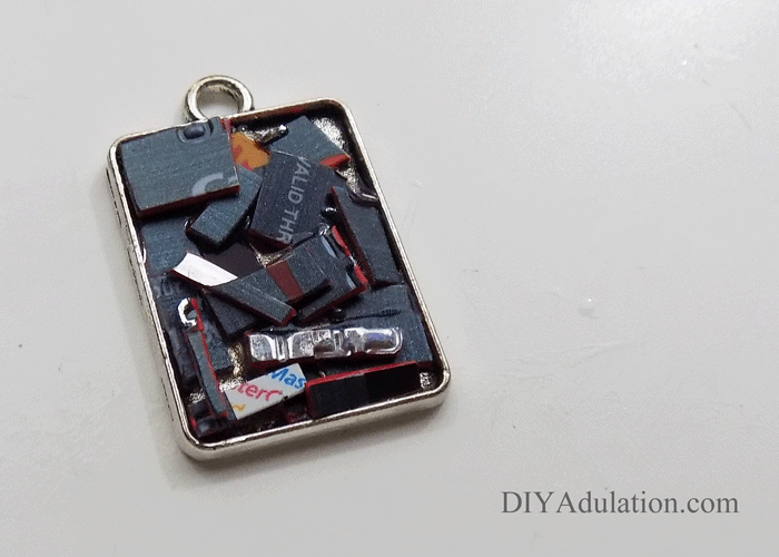 Cut up pieces of credit card inside rectangle keychain base