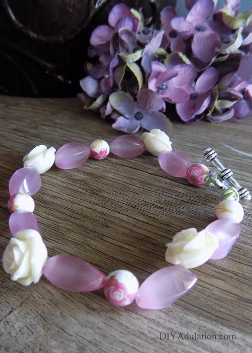 Pink floral beaded bracelet on wooden table