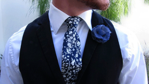 Close up of man's chest with a blue flower boutteniere