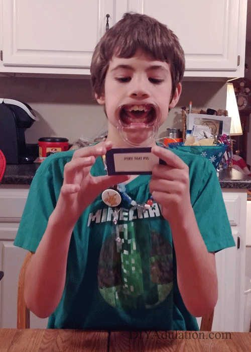 Child holding a card with a plastic opener in his mouth