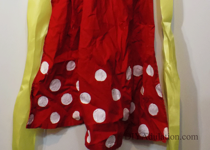 Close up of bottom of red apron with white polka dots