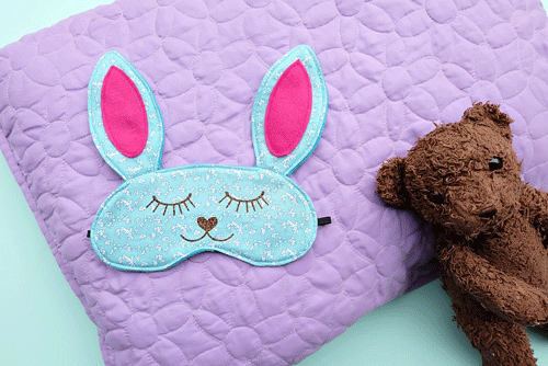 Kids bunny sleep mask on lavender blanket with a teddy bear