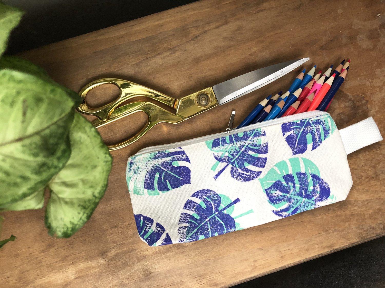 Palm leaf pencil bag next to gold handled scissors