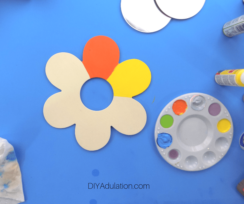 Wooden Flower with Orange and Yellow Painted Petals next to Paint Pallet