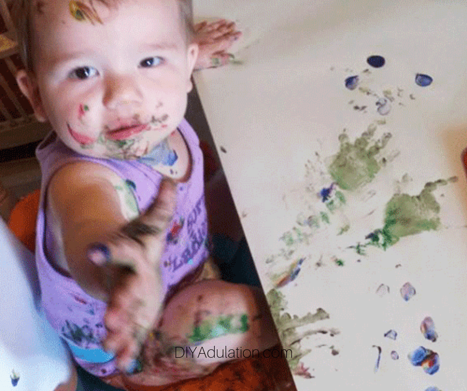Baby Covered in Paint Next to Painted Paper