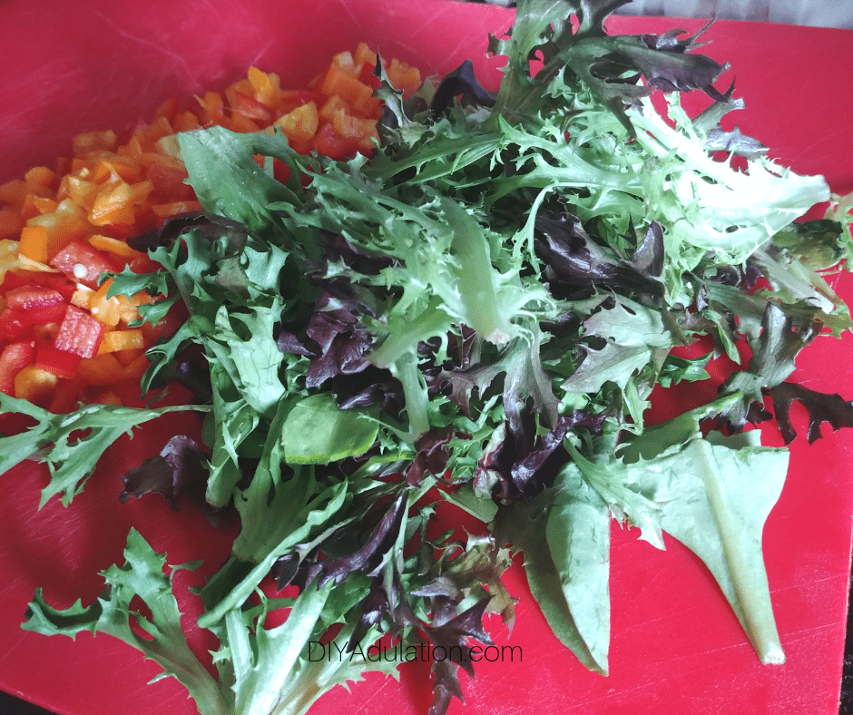 Baby Greens next to Diced Mini Sweet Peppers on Cutting Board