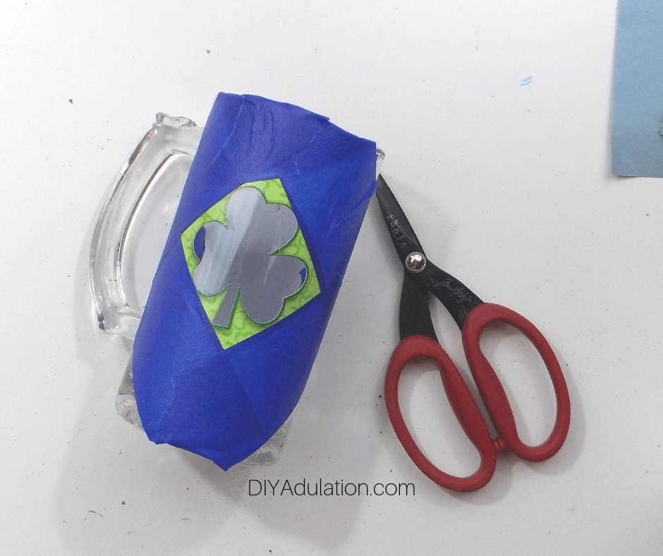 Blue Painters Tape Around Edges of Shamrock Sticker Negative on Clear Glass Stein next to Scissors