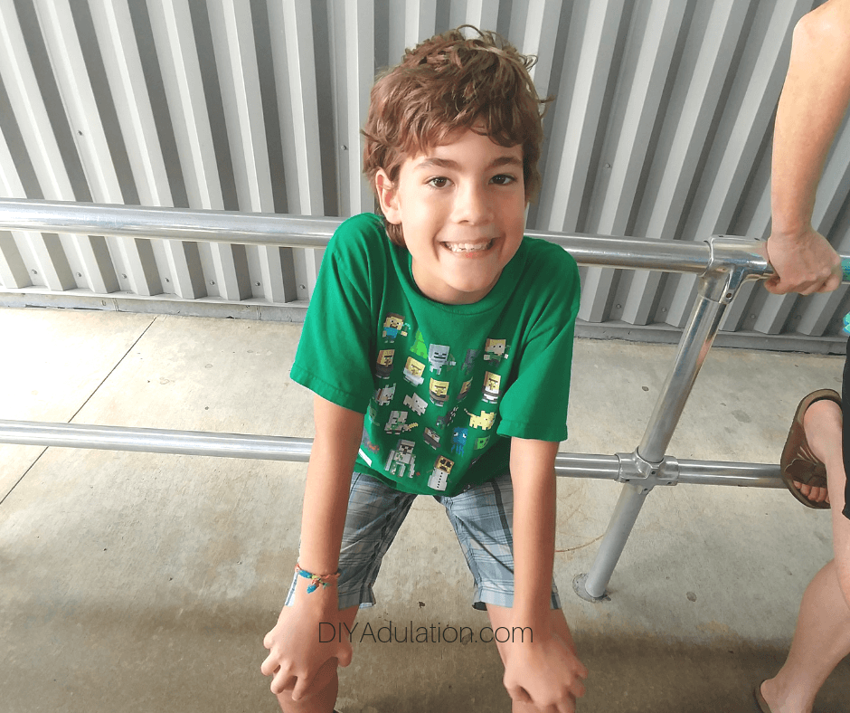 Boy Sitting on Metal Railing