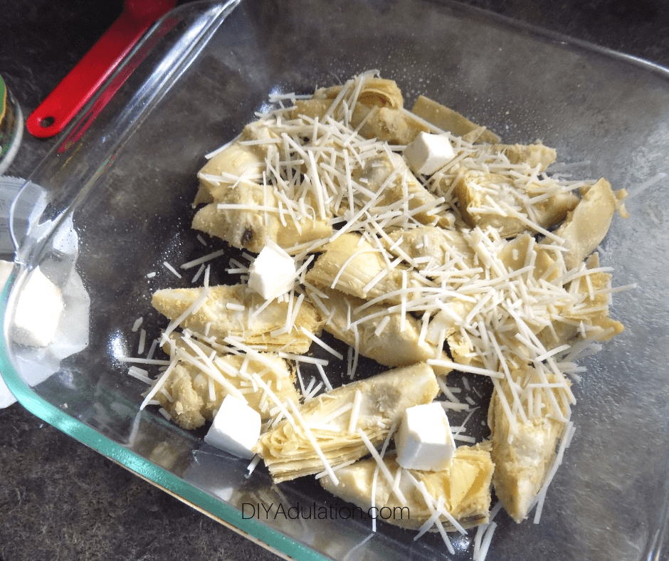 Butter Cubes on Cheese and Artichoke in Glass Baking Dish
