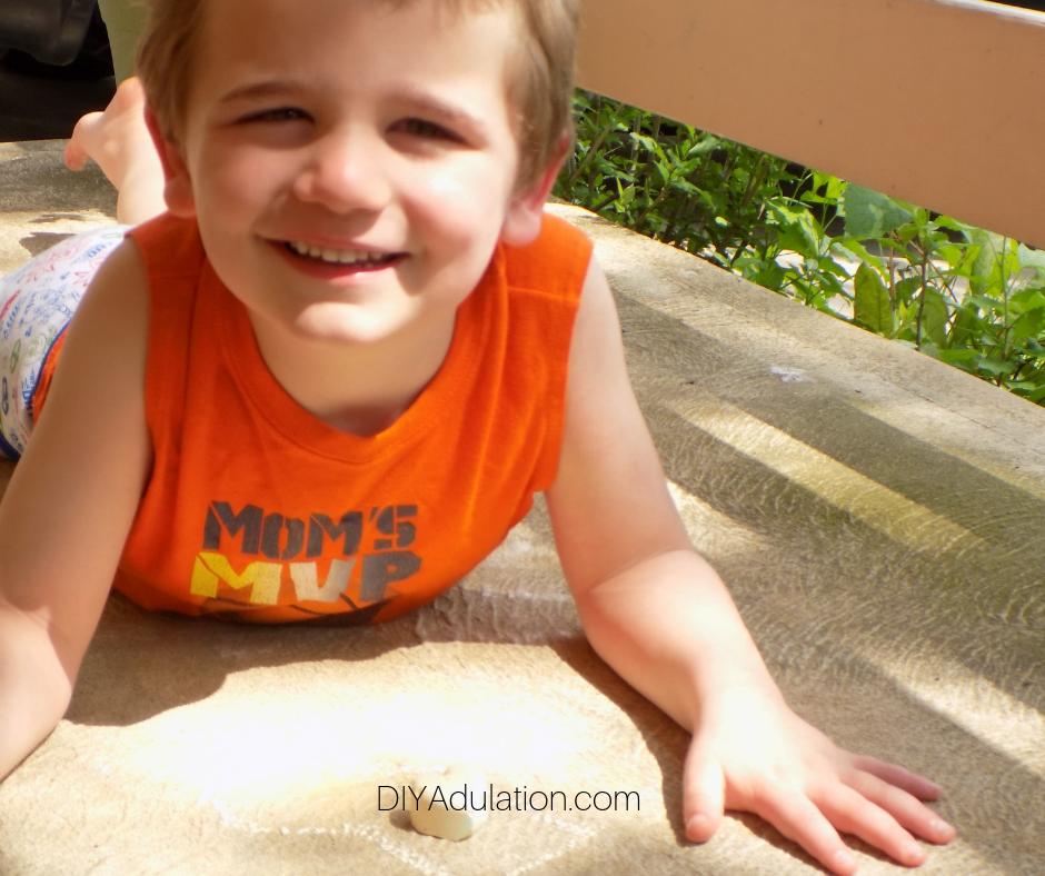 Child playing with sidewalk chalk