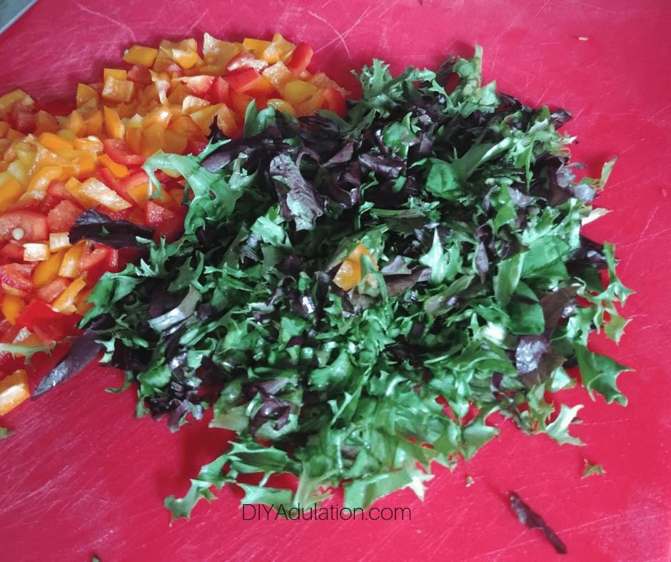 Chopped Baby Greens next to Diced Mini Sweet Peppers on Cutting Board