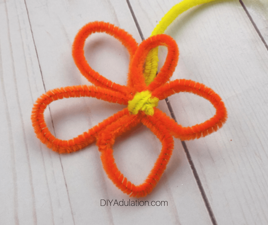 Close Up of End of Yellow Pipe Cleaner Wrapped Around Center of Orange Pipe Cleaner Flower