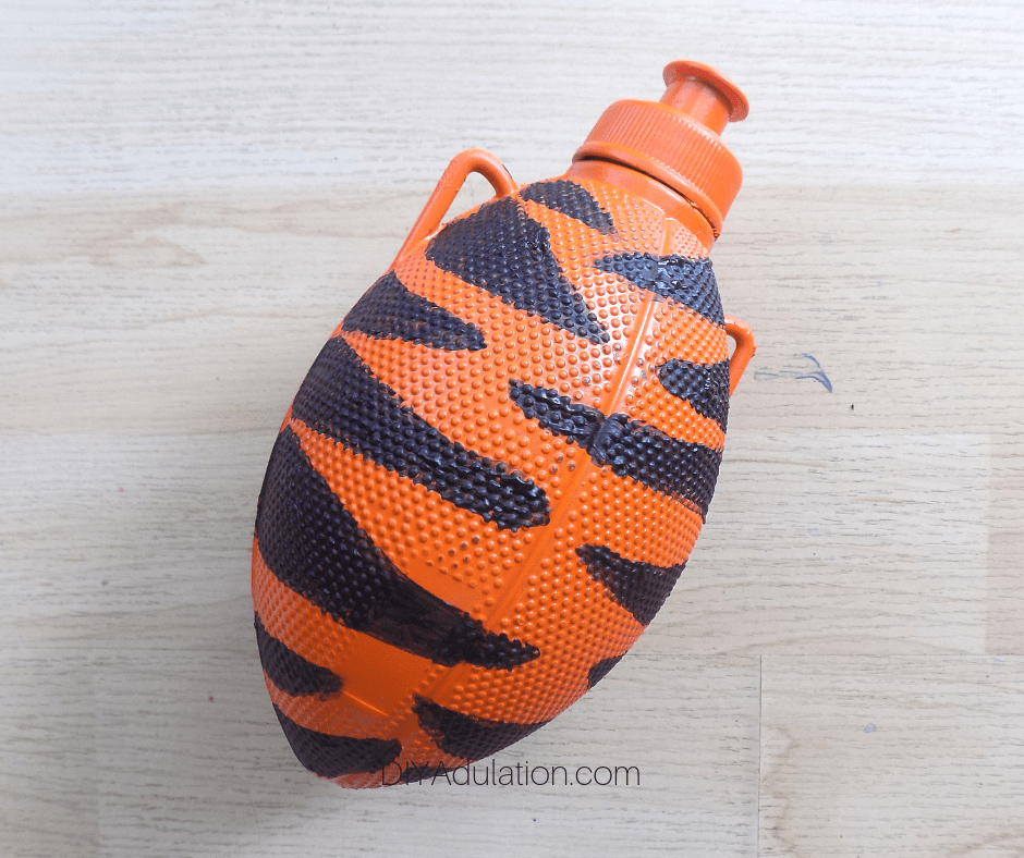Close Up of Orange Spray Painted Football Water Bottle with Dark Black Stripes