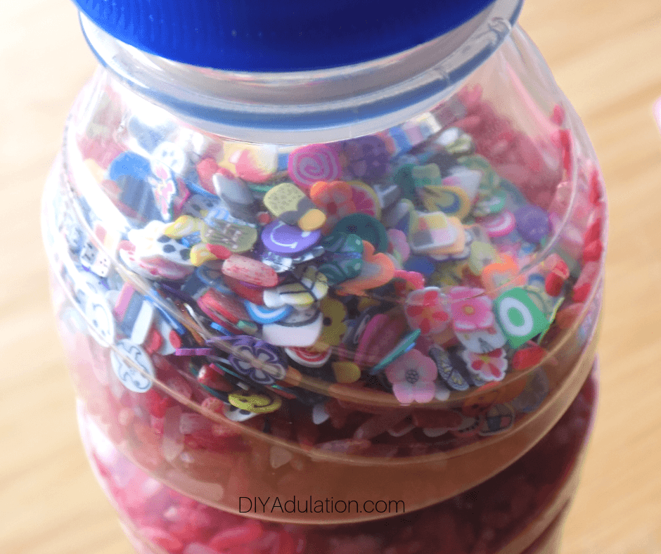 Close Up of Small Charms on Rice in Plastic Bottle