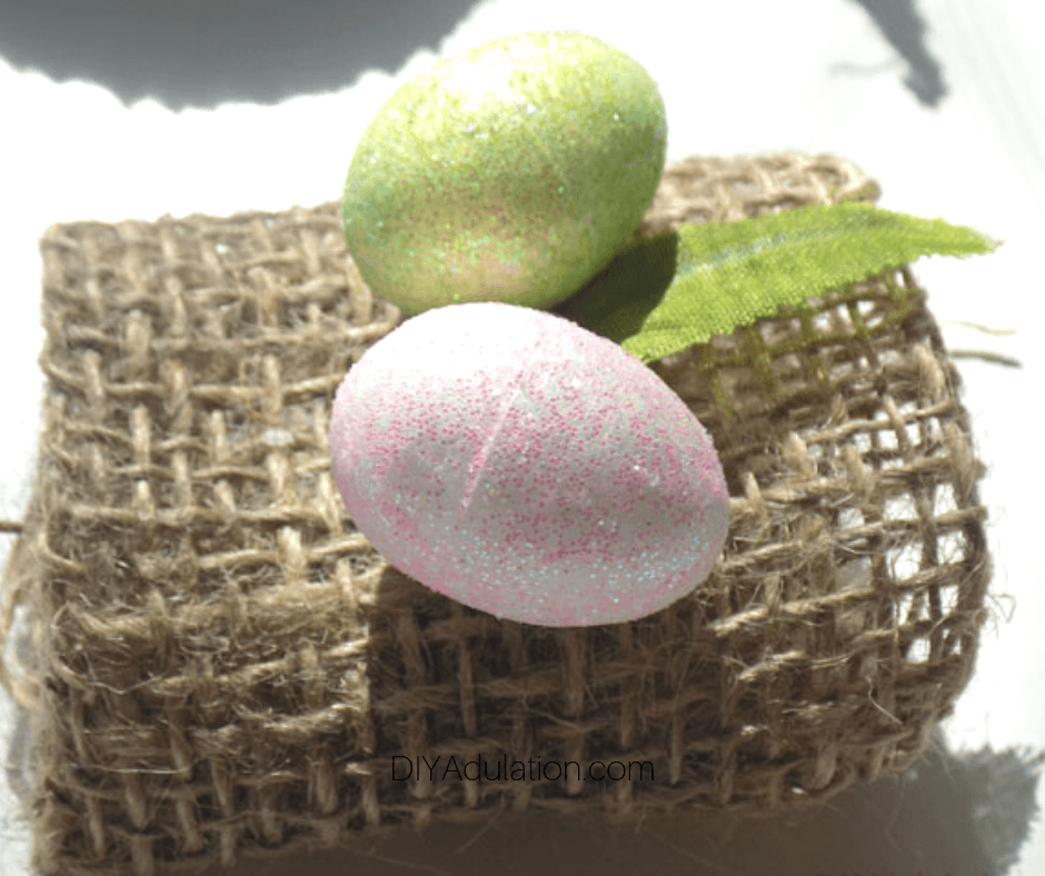 Close up of Glitter Eggs and Leaf on Burlap