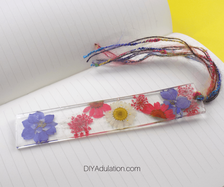Close up of Pressed Flower Bookmark with Tassels on Lined Journal