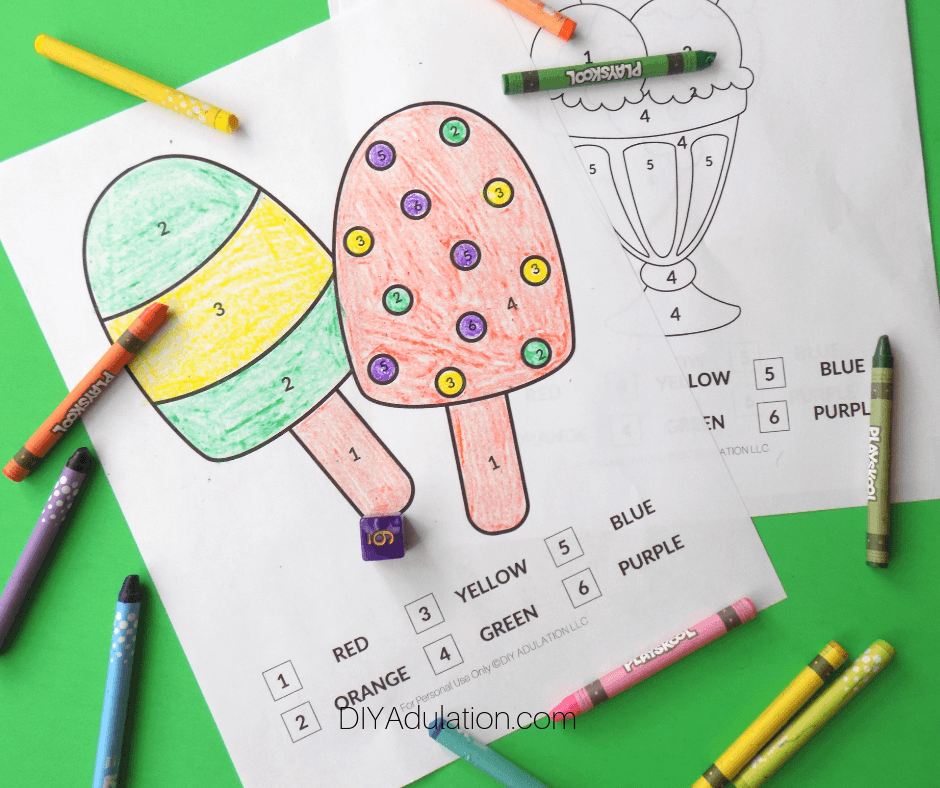 Colored Ice Cream Color by Number Sheet Next to Uncolored Pages and Crayons