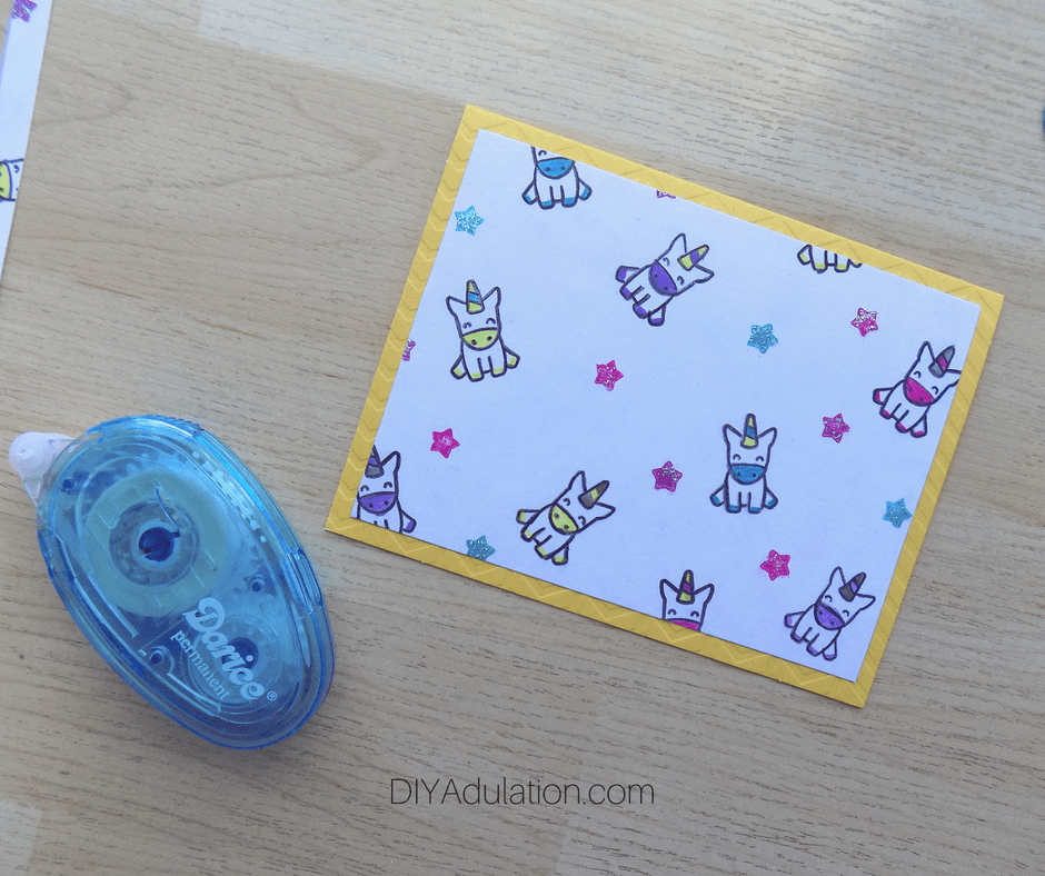 Colorful Unicorns Cardstock Attached to Yellow Card Next to Glue Runner