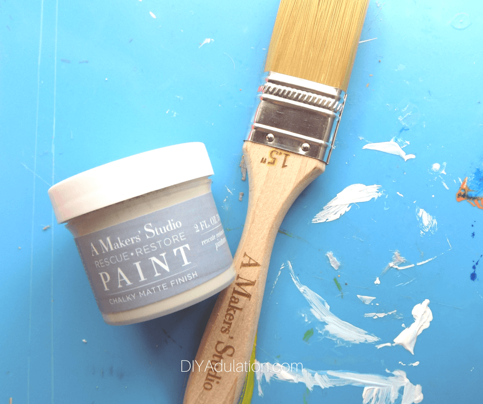 Container of Paint Next to Wooden Paint Brush