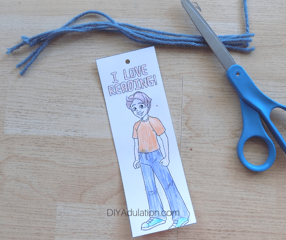 Cut Lengths of Yarn Next to Colored Charlie Tractor Bookmark