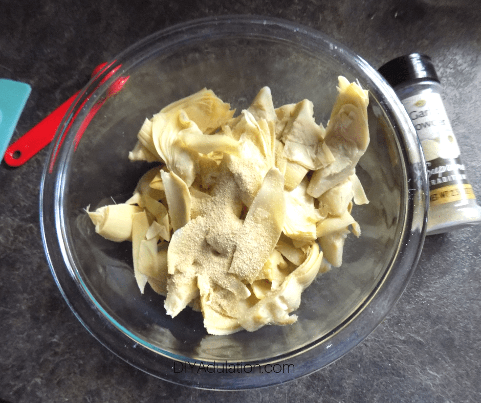Garlic Powder and Quartered Artichoke Hearts in Glass Bowl