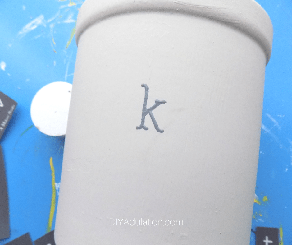 Gray painted letter K on painted crock