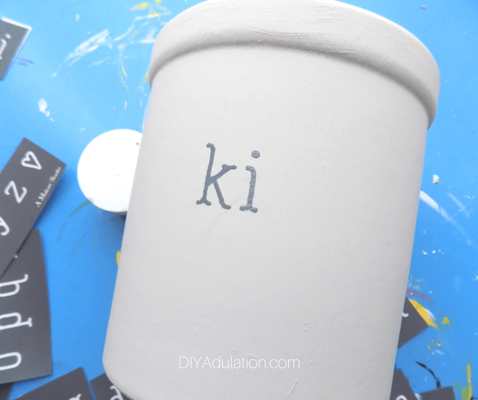 Gray painted letters K and I on painted crock