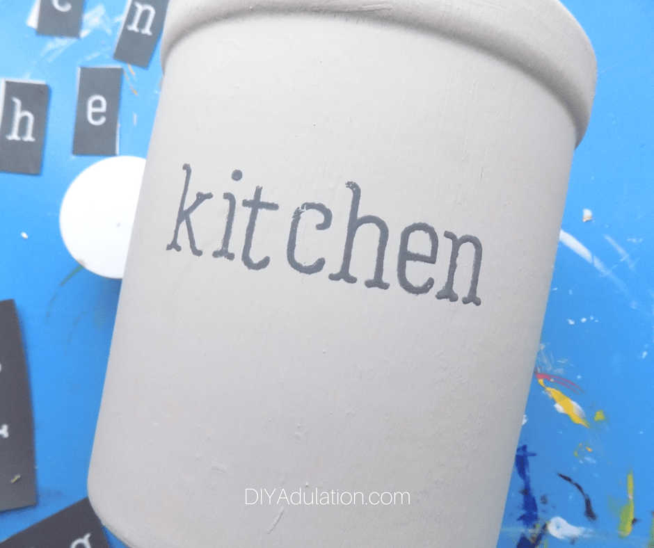 Gray painted word Kitchen on painted crock