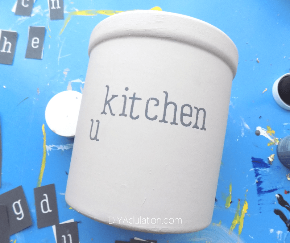 Gray painted word Kitchen with a letter U underneath on painted crock