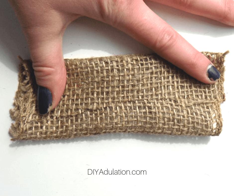Hand Folding Piece of Burlap