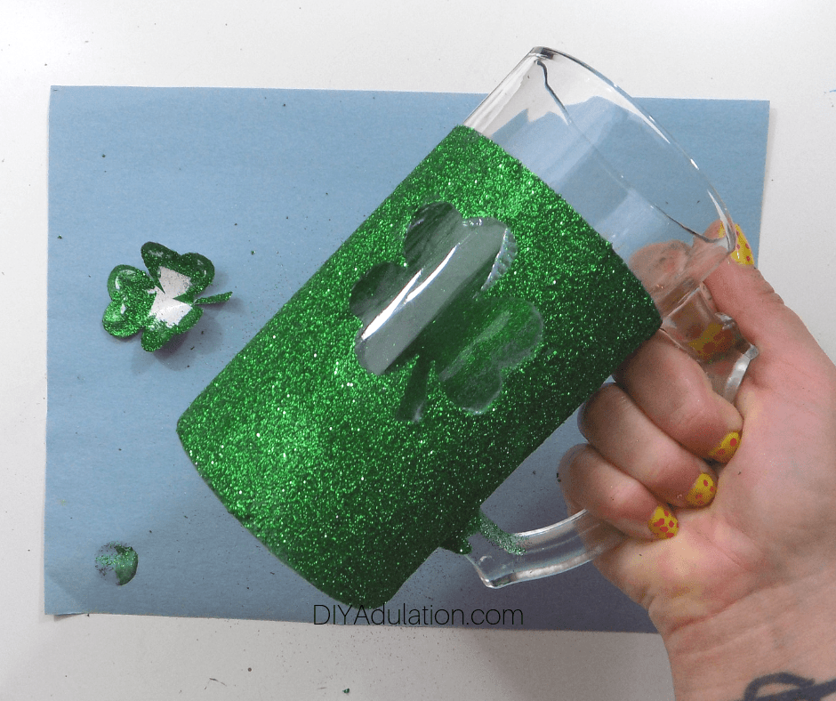 Hand Holding Green Glitter Stein with Blue Tape Removed and Shamrock in Center