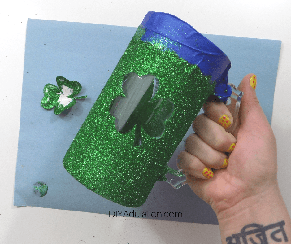 Hand Holding Green Glitter Stein with Shamrock in Center