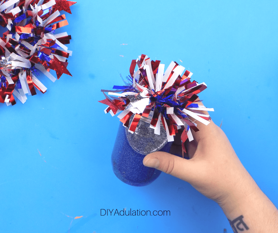 Hand Holding Patriotic Glitter Sensory Jar with Garland on Lid