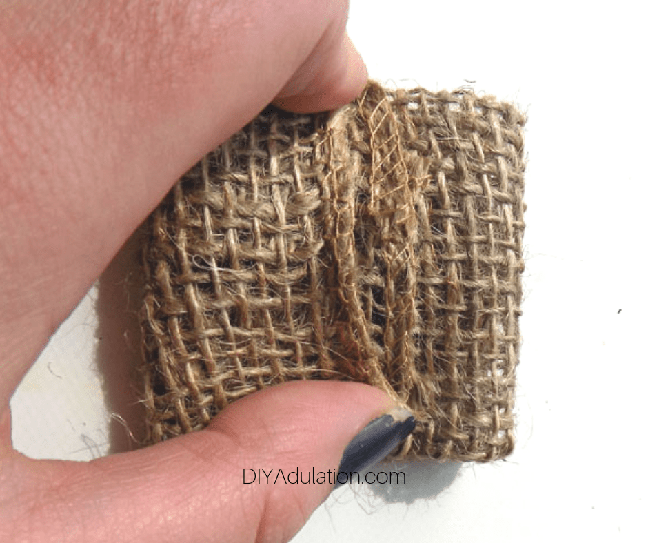 Hand Holding Small Folded Piece of Burlap