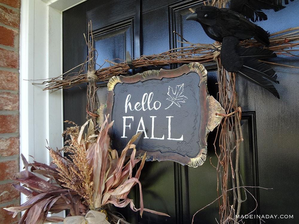 Wooden stick hello fall wreath hanging on door