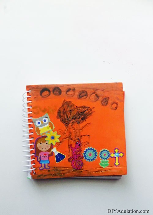 Orange Spiral Bound Notebook with stickers on the cover