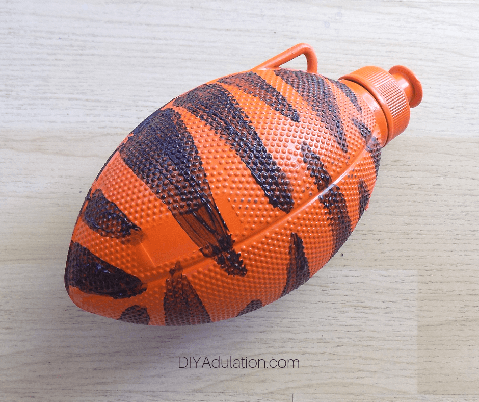 Orange Spray Painted Football Water Bottle with Black Stripes on Back