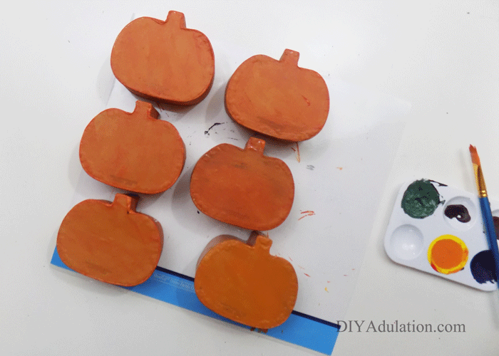 Orange Painted Pumpkins next to a paint pallet