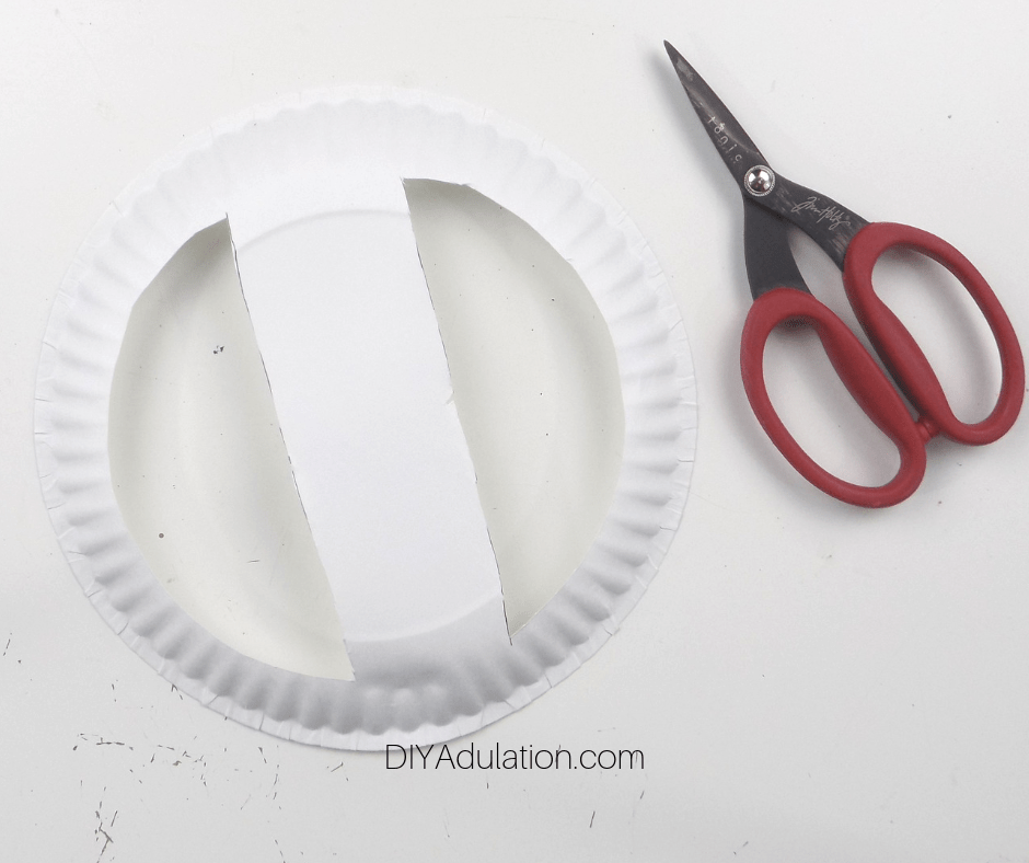 Paper Plate Half Circles Cut out of It next to Scissors