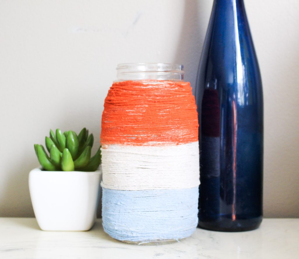 Patriotic mason jar with twine next to bottle and plant