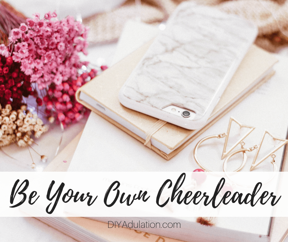 Phone on Stack of Books Next to Flowers with text overlay_ Be Your Own Cheerleader