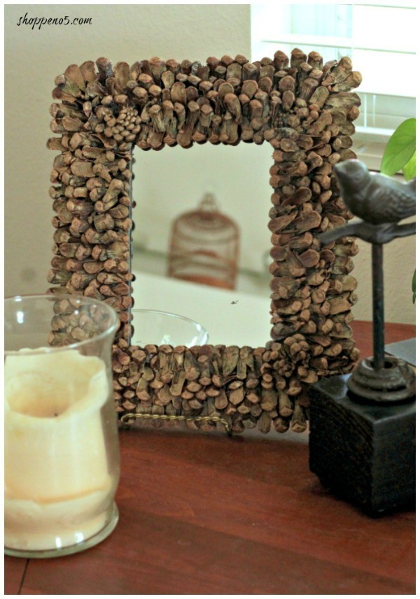 Small mirror next to candle and bird decoration