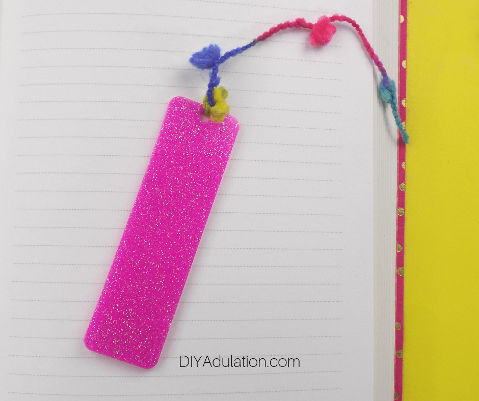 Close Up of Pink Glittery DIY Bookmark on Lined Notebook