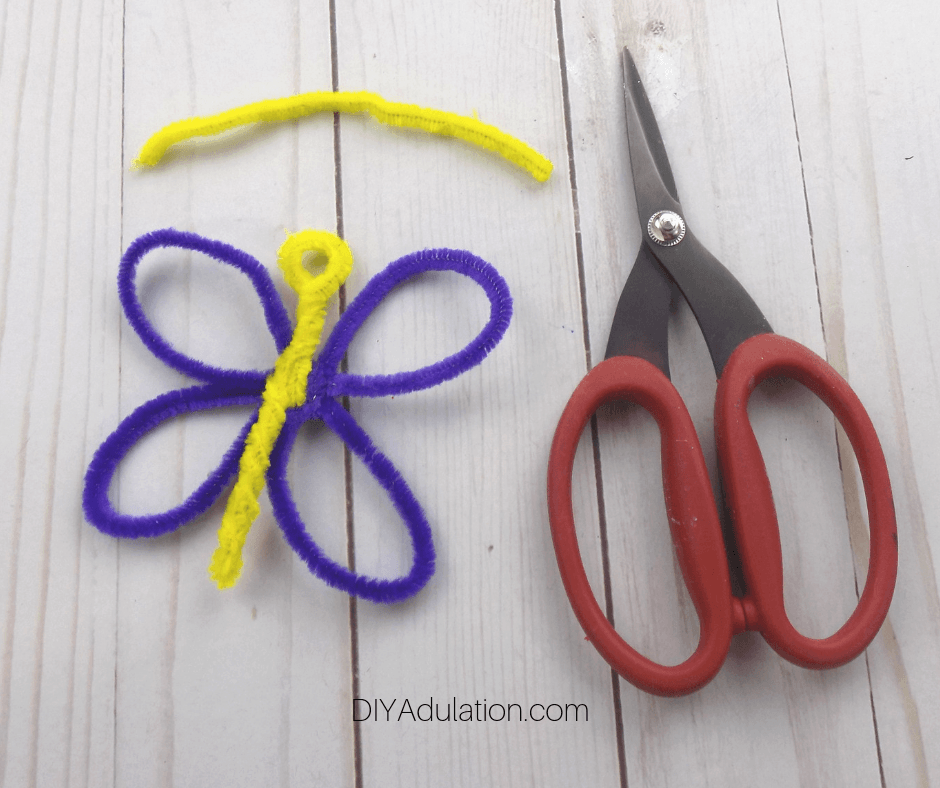 Pipe Cleaner Butterfly next to Small Piece of Yellow Pipe Cleaner and Scissors