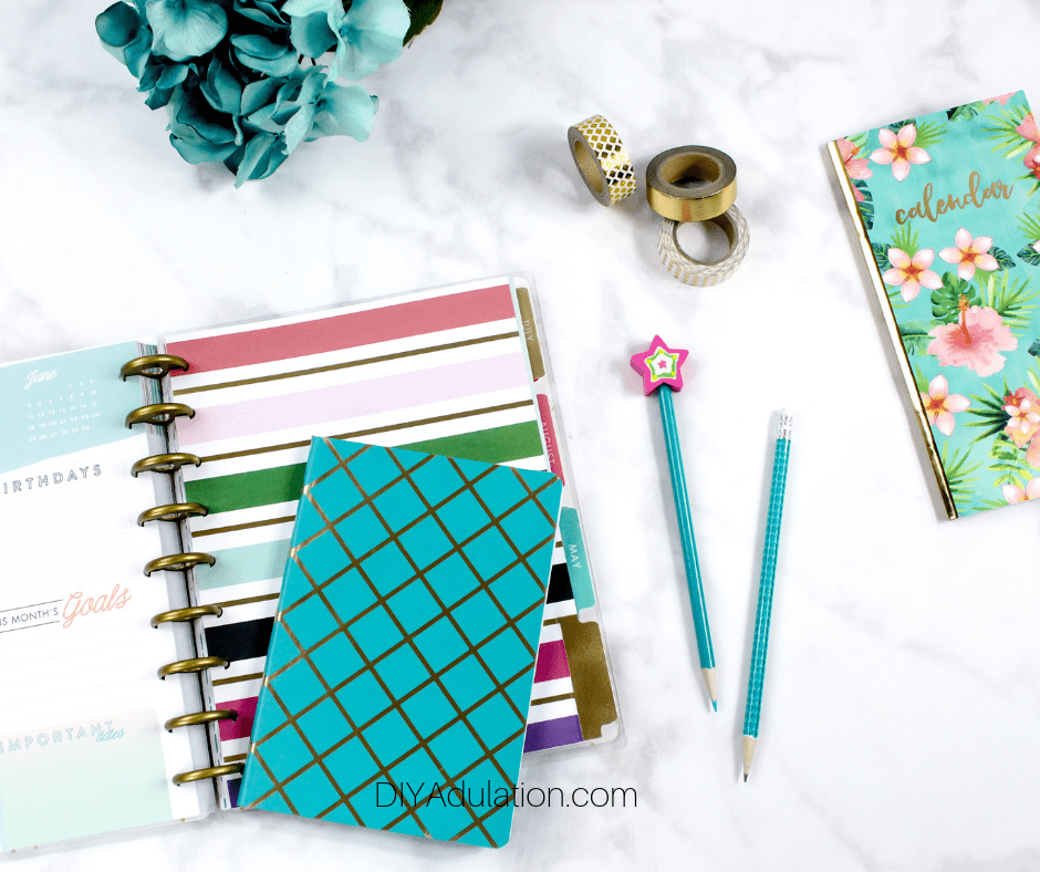 Planner and Accessories next to Flowers