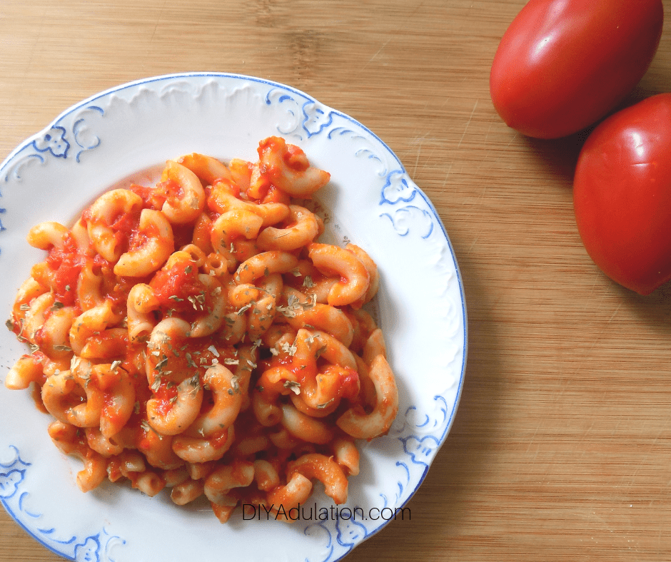 Plate of Macaroni and Tomatoes next to Fresh Tomatoes