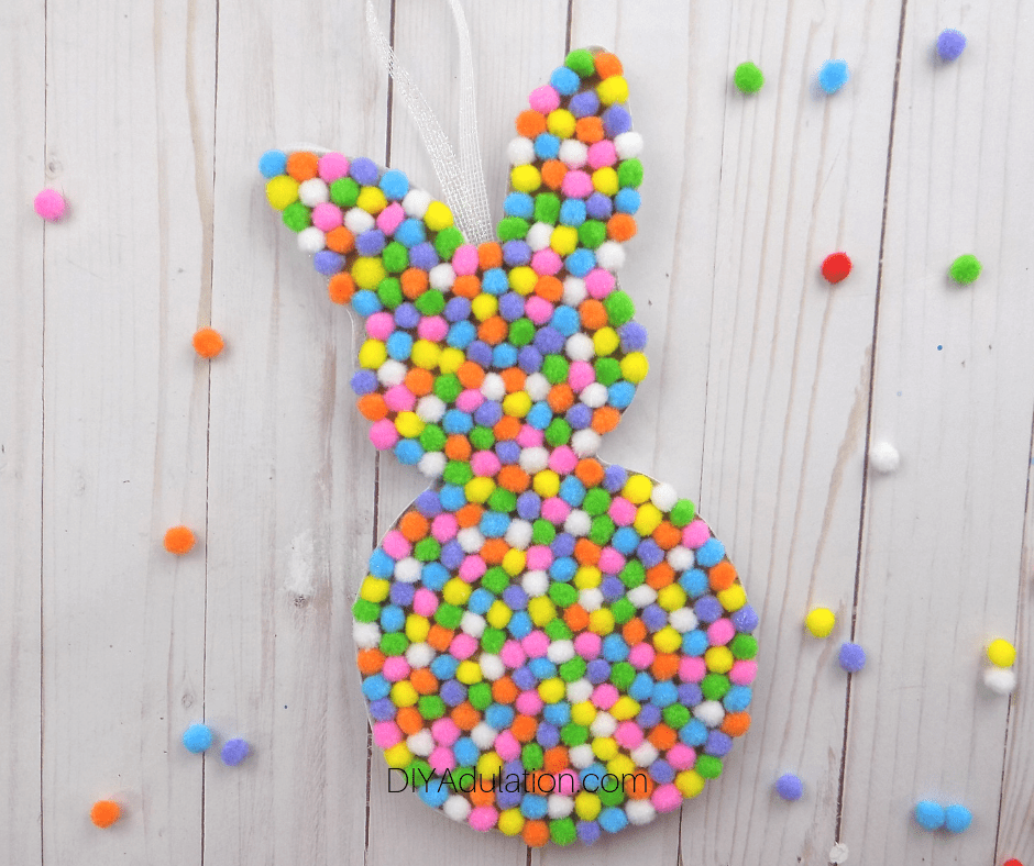 Pompom Bunny on Wood Background with Pompoms