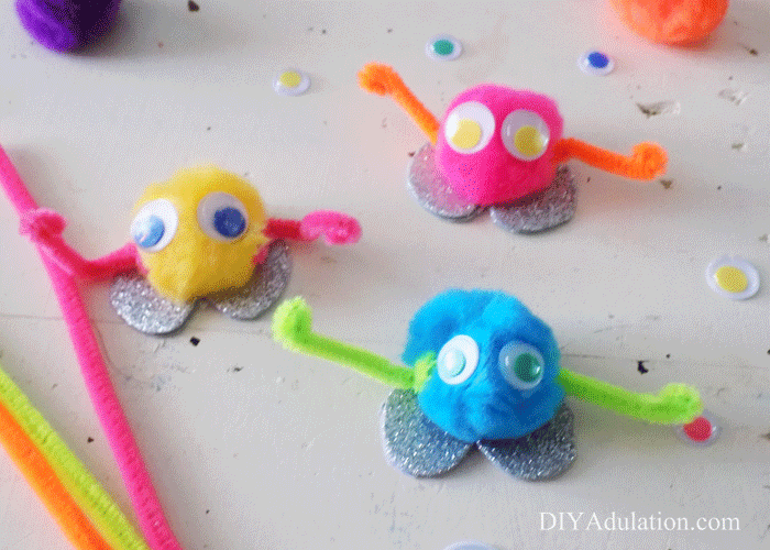 Pompom monsters next to craft supplies