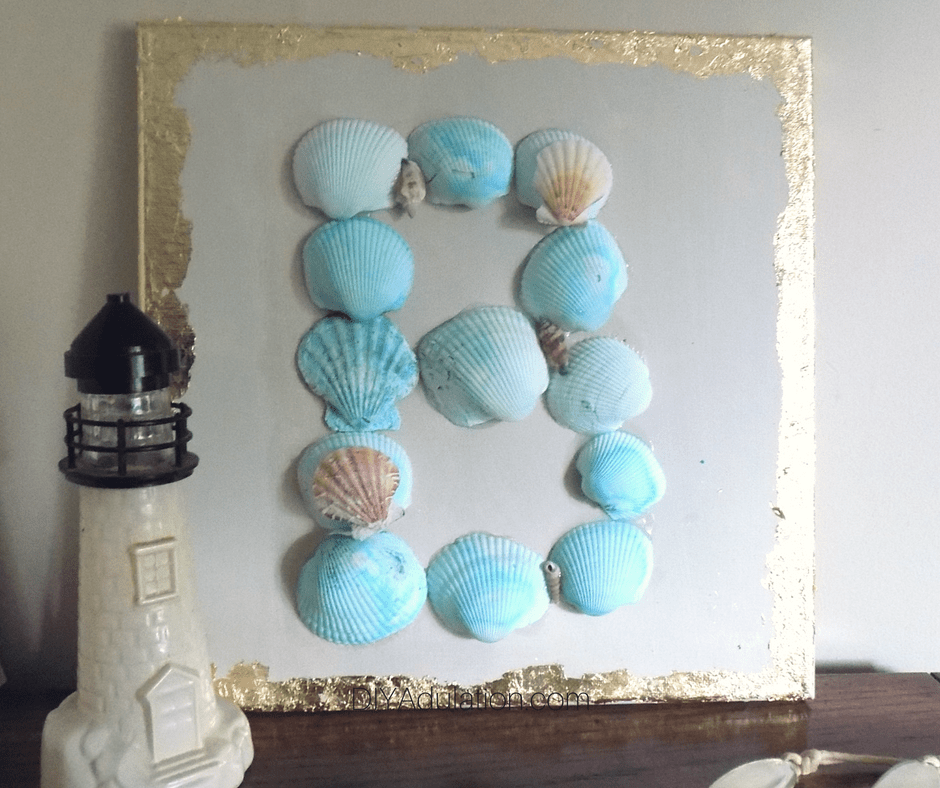 Seashells Monogram Wall Art Next to Lighthouse Sculpture